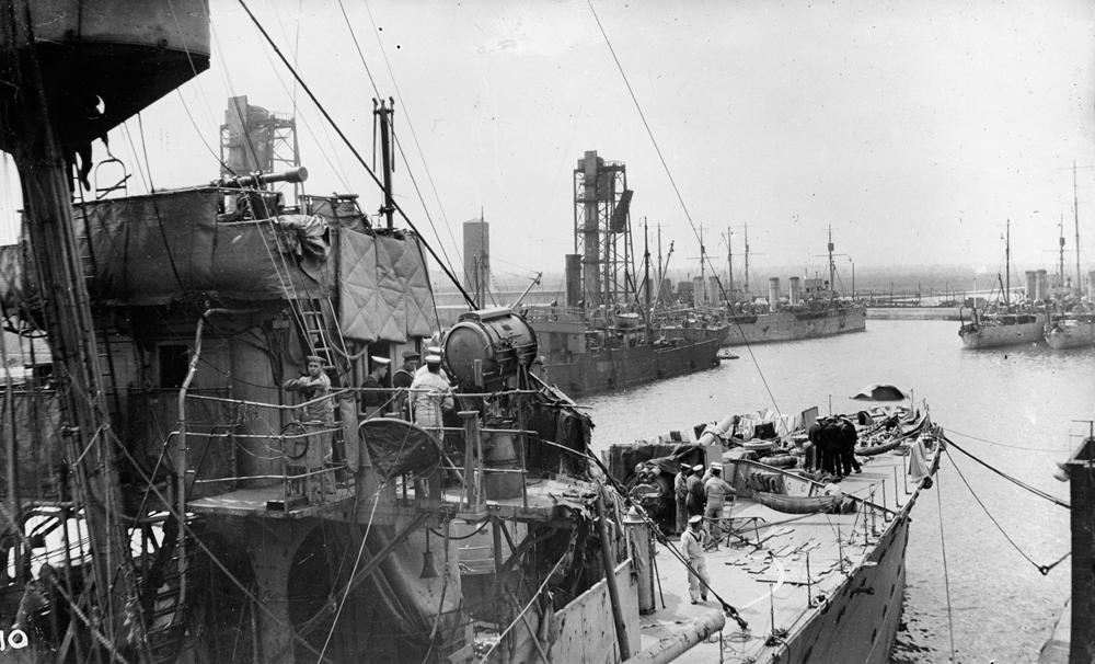 Damage to the starboard side of the forebridge of HMS Chester sustained during the battle of Jutland. Several sailors can be seen on deck whilst various merchant ships can be seen in the background. Boy (1st Class) Jack Travers Cornwell was posthumously awarded the Victoria Cross for remaining at the forward gun on board the cruiser. The ship was badly shelled by four German cruisers and Cornwell's position was hit four times, killing all the crew apart from Cornwell. The badly wounded boy sailor was taken back to Grimsby where he died on 2 June.