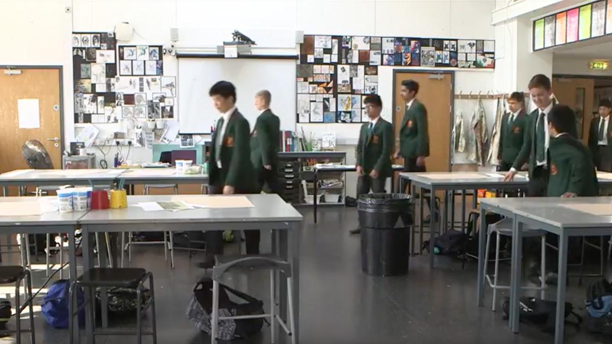 School children walking into a classroom